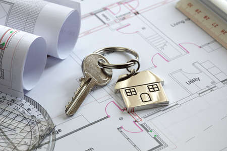 relocating: House keys on a house plan blueprint concept for new house design or home improvement