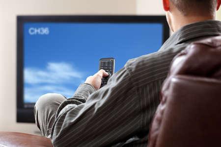 Muž sedící na pohovce sledování televize drží dálkové ovládání