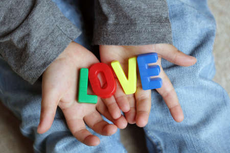l hand: Little boy holding the word love made from childrens  letter magnets
