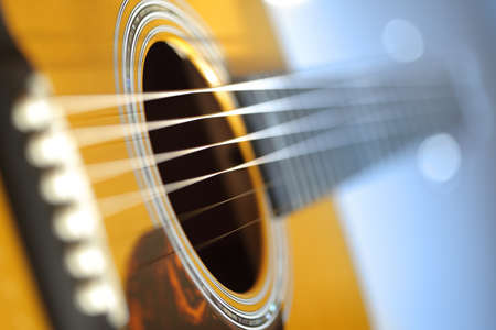 acoustic guitar: Acoustic guitar with very shallow depth of field, focus on strings above sound hole