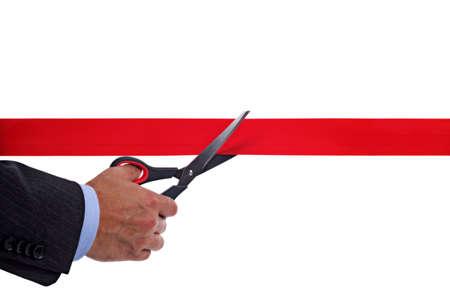 tijeras cortando: Corte una cinta roja con un par de tijeras de Empresario Foto de archivo