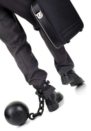 Ball and chain restraining a businessman as he walks away with a briefcase photo