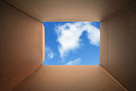 blue sky thinking: Inside a cardboard box concept for moving house, creativity or thinking outside the box Stock Photo