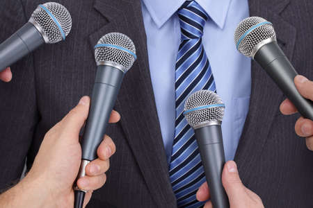 using voice: Press conference with media microphones held in front of business man, spokesman or politician Stock Photo