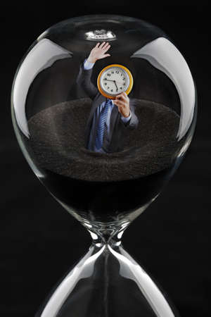 beat the clock: Deadline concept - businessman running out of time sinking into hourglass trying to beat the clock Stock Photo