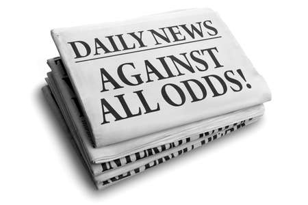adversity: Daily news newspaper headline reading against all odds concept for conquering adversity