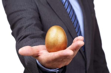 retirement nest egg: Businessman holding a golden egg concept for wealth, investment and retirement