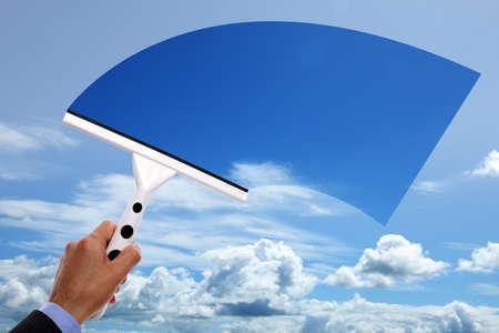 contaminacion ambiental: Limpiador de ventanas utilizando una rasqueta para limpiar el cielo azul arriba Foto de archivo