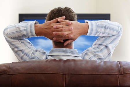 Man sitting on a sofa watching tv with hands folded behind his head photo