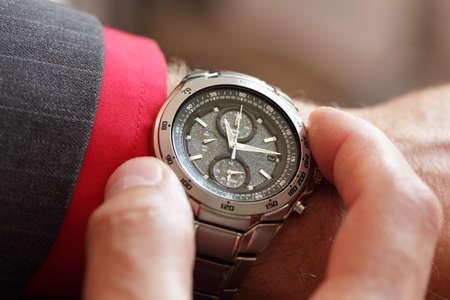 mans watch: Empresario comprobando la hora en su reloj de pulsera