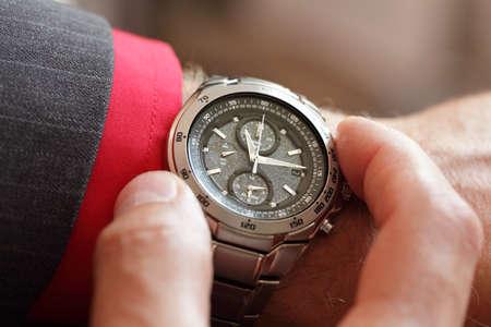 Zakenman het controleren van de tijd op zijn polshorloge