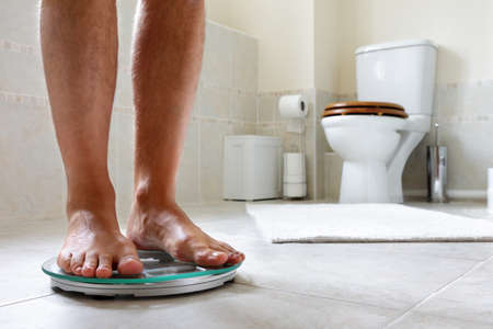 Standing on bathroom scale concept for dieting, slimming or overweight photo
