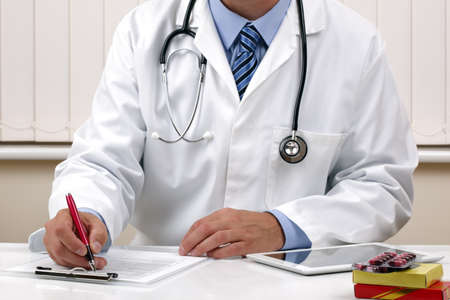 Doctor writing patient notes on a medical examination form or prescription photo