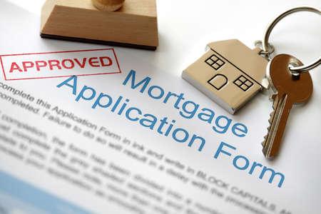 Solicitud de préstamo hipotecario aprobada con llave de la casa y sello de goma