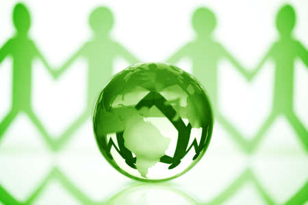 hands holding earth: Paper chain men holding hands around a green globe concept for partnership, teamwork or global community