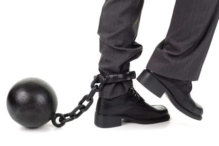 Ball and chain restraining a businessman as he tries to walk photo