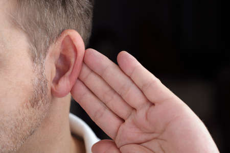 Man with hand on ear listening for quiet sound or paying attention Stock Photo - 25087910