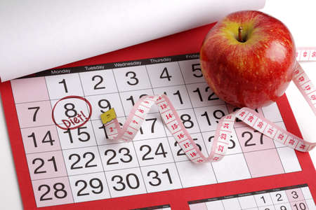 Dieting concept apple and tape measure on a calendar with a date to start a diet photo