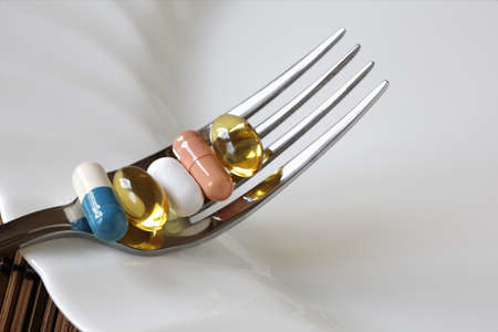 nutritional supplement: Medicine and nutritional supplement on a fork Stock Photo