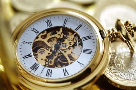 Zakhorloge en gouden munten concept voor investering of tijd is geld Stockfoto