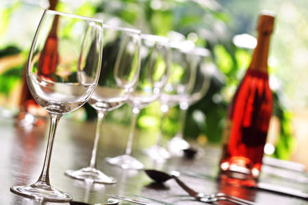 Restaurant table with silverware, wine and wine glasses photo