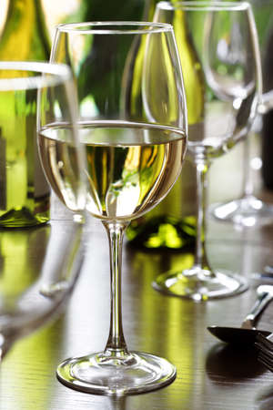 stereotypically: Restaurant table with white wine, silverware and wine glasses
