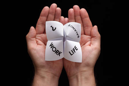 cootie catcher: Origami fortune teller in cupped hands concept for work life balance choices Stock Photo