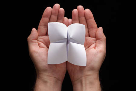 cootie catcher: Origami fortune teller with blank choices in cupped hands
