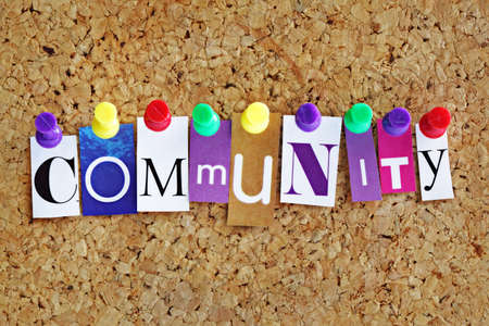 Community concept letters attached to a cork noticeboard with thumbtacks