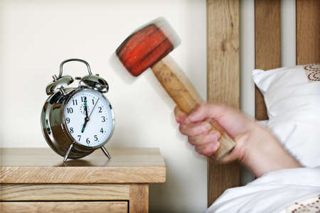 Smashing alarm clock with hammer concept for sleeping in, tired, exhaustion or waking up photo