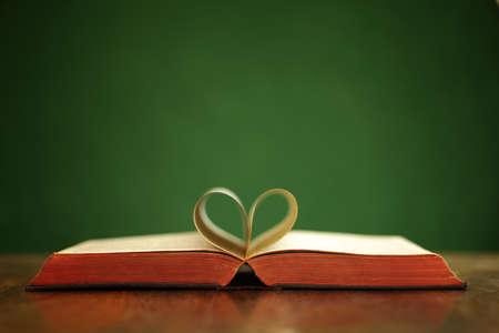 Bibel auf dem Tisch mit Seiten in Herzform gefaltet