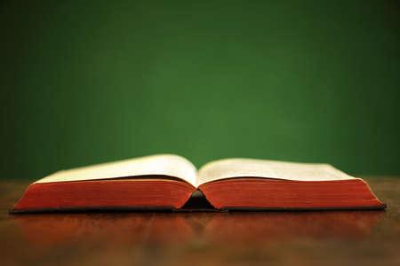bible ouverte: Bible sur la table sur le mur vert et l'espace de copie Banque d'images