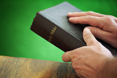 Bible with mans hand resting on the cover whilst holding in front of a green wall photo
