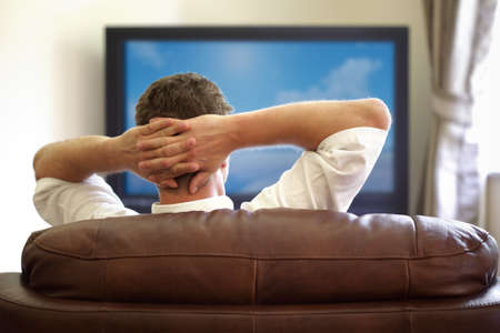 flat screen tv: Man sitting on a sofa watching tv with hands folded behind his head Stock Photo