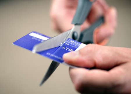 overspending: Hands cutting a credit card with scissors