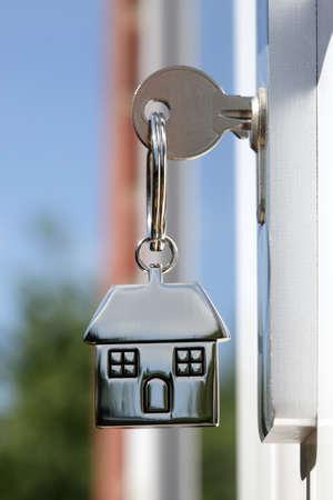 claves: Casa llave en un llavero de plata con forma de casa en la cerradura de una puerta Foto de archivo