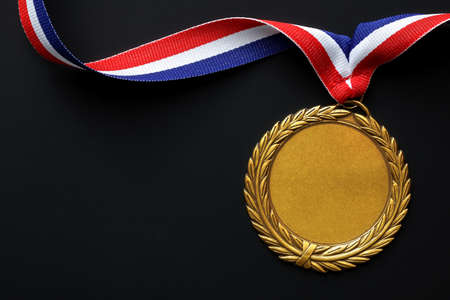 Gold medal on black with blank face for text, concept for winning or success photo