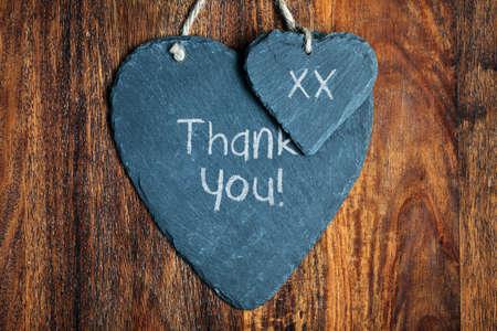 merci: Merci de note �crite � la craie sur un coeur en ardoise accroch�e � un fond en bois