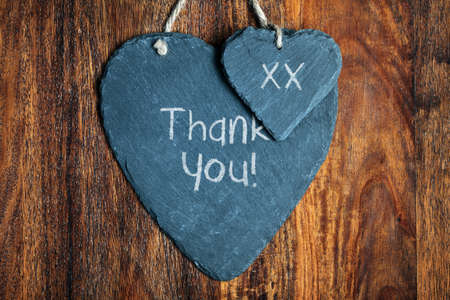 Thank you note written in chalk on a slate heart hanging on a wooden background photo