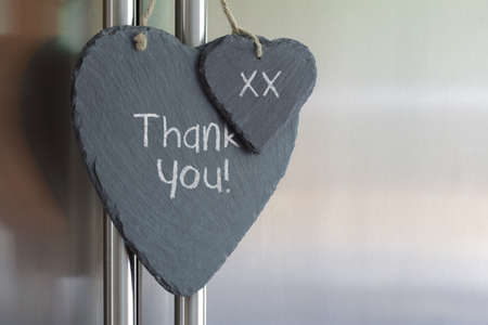 thank you note: Thank you note written in chalk on a slate heart hanging on a refrigerator door Stock Photo