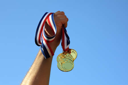 Winning at sport event, hand holding gold medals