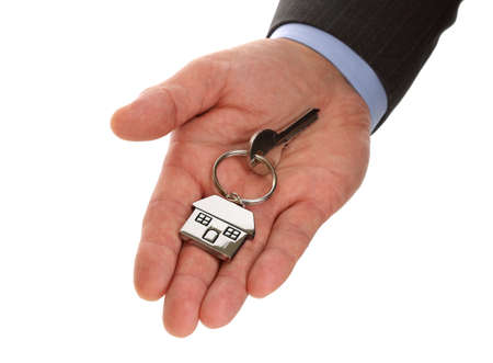 differential focus: Estate agent giving house keys on a silver house shaped keychain concept for moving, selling or buying a house