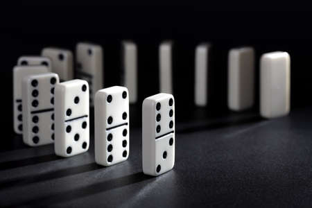dominoes: Dominoes lined up ready to fall concept for domino effect, balance and risk