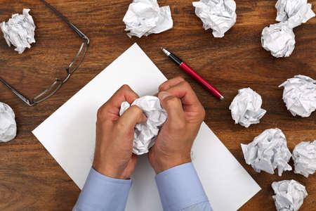 persona escribiendo: Papel arrugado y empresario rompiendo otra bola de papel de la pila Foto de archivo
