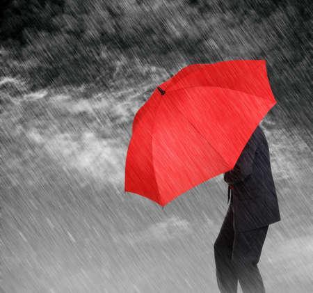 景気後退や不況などから保護するため嵐概念から彼自身を保護する赤い傘を持ったビジネスマン