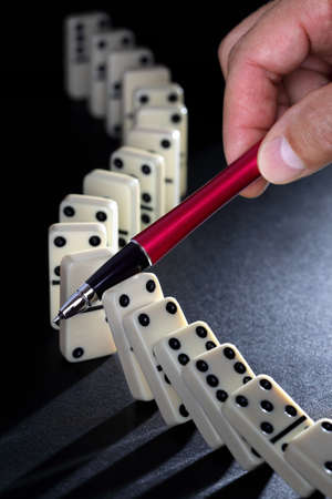 Stop the domino effect concept for solution to a problem photo