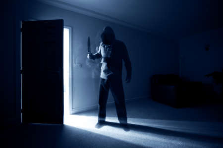 ominous: Burglar breaking into a house and threatening with a knife Stock Photo