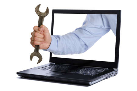 Hand holding spanner through the screen of laptop photo