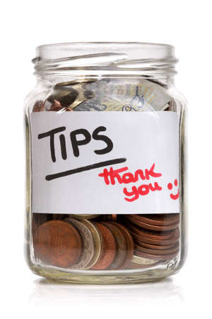 Tip jar with British currency and label saying thank you photo
