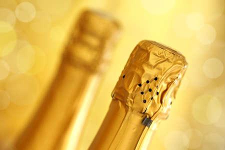 celebration champagne: Champagne bottles over a defocused sparkling gold background Stock Photo